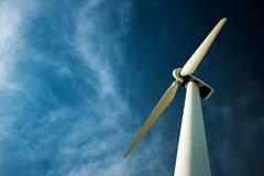 Lonely wind turbine and the dark cloudy blue sky. Stock Photos