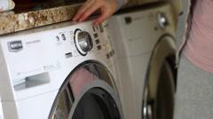 Woman turns on washing machine Stock Footage