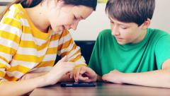 Boy and girl playing a game with a mobile phone Stock Footage
