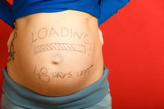 Pregnant woman with loading concept painted on her belly Kuvituskuvat