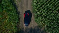 Vintage car aerial shot, driving on dirt road in wilderness, top camera view Stock Footage