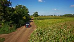 Vintage car aerial shot, driving on dirt road in wilderness chase camera view Stock Footage