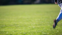 Kid on soccer field running around and kicking ball - stock footage