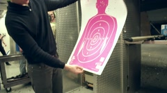 Man admiring his shooting at a gun range with pink target Stock Footage