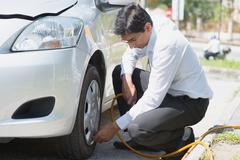asian filling air to the car tires. - stock photo