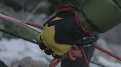 A man adjusts rigging on a climbing expedition - stock footage