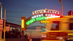 Firetruck driving by Santa Monica Pier entrance sign in Los Angeles, California Stock Footage