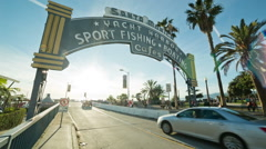 Cars entering Santa Monica Pier entrance sign in Los Angeles, California Stock Footage