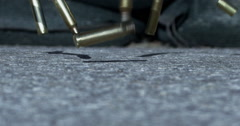 Slow motion bullets landing on the asphalt in front of sand bags - war zone - stock footage