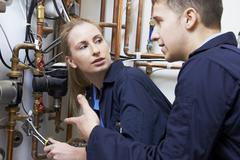 Female trainee plumber working on central heating boiler Stock Photos
