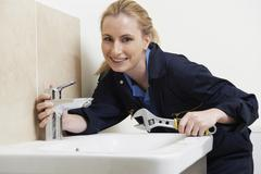 Female plumber working on sink using wrench Stock Photos