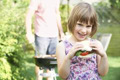young girl eating beefburger at family barbeque - stock photo