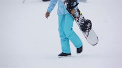 Girl in blue pants going with snowboard Stock Footage