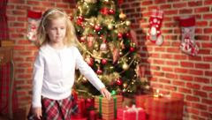 Little girl put large giftbox under christmas tree Stock Footage
