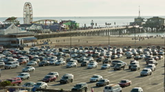 Ferris wheel roller coaster parking lot cars parked Pacific Park LA California Stock Footage