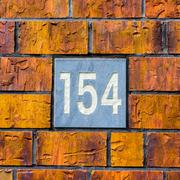 House number one hundred and fifty four, engraved in natural stone. - 154 Stock Photos