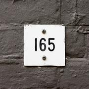 House number one hundred and sixty five, engraved in a plastic plate. -165 Stock Photos
