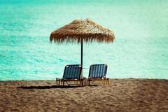 Beach sun beds and straw umbrella on the beach Stock Photos