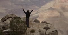 Young man holds hands in the air in front of Grand Canyon Stock Footage