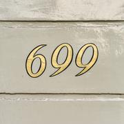 Gold colored house number six hundred and ninety nine - 699 Stock Photos
