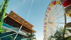 Panning shot roller coaster ferris wheel Pacific Park Santa Monica pier Stock Footage