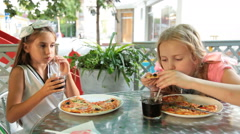 Little girls eating pizza and drinking cola drink at outdoor cafe Stock Footage