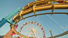 Roller coaster ride spinning ferris wheel Pacific Park on Santa Monica pier Stock Footage