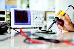 soldering electronic parts on a printed circuit board - stock photo
