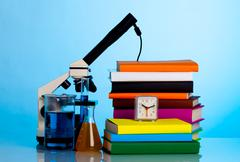 microscope, books and chemical ware on a school table - stock photo