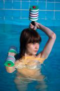 Pretty girl doing aqua aerobic exercise Stock Photos
