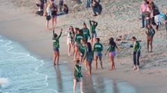 Team pretty teenage girls having fun beach green uniform jackets LA California Stock Footage