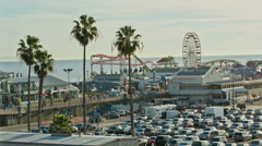 Ferris wheel spinning parking lot palm trees Pacific Park Santa Monica LA Stock Footage