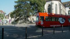 Red tram in front of church Stock Footage