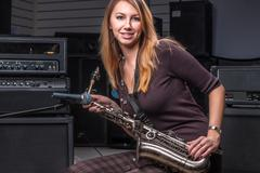 Pretty woman with saxophone - stock photo