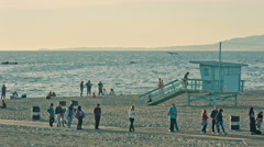 Lifeguard hut tower beach tourists walking sand Pacific Ocean Santa Monica LA Stock Footage