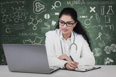 doctor working with laptop and clipboard - stock photo