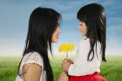 happy child giving flower to her mother - stock photo