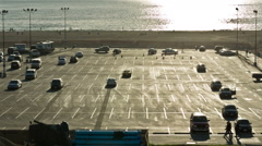 Parking Lot on Beach - Cars Parked at Ocean with Silhouettes of People Walking Stock Footage