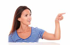 charming lady in blue t-shirt pointing to her left while selecting in white b - stock photo