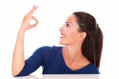 lovely woman making an ok sign while looking to her left in white background  - stock photo
