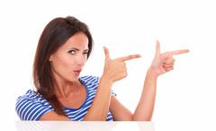 attractive winking woman pointing to her left in white background - copyspace - stock photo