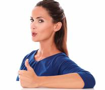 cute girl with thumb up gesturing great job while looking at you in white bac - stock photo