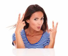 Lovely hispanic making a victory sign and feeling a winner while looking at c Stock Photos