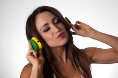 young pretty latino woman listening to colorful dj style and wearing sunglass - stock photo