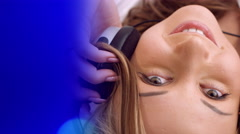 Happy young woman listening music and defocused blue light - stock footage
