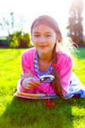girl looking through a magnifying glass on the grass - stock photo