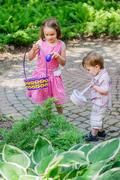 little boy and girl on an easter egg hunt - stock photo