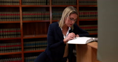 Librarian reading and noting in book - stock footage