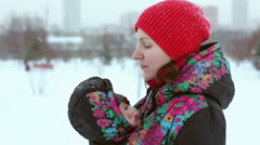 Young mother in a winter park with a baby in a sling-jacket Stock Footage
