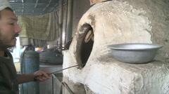 Afghan cook prepares food in outdoor oven at food market in Kabul Afghanistan - stock footage